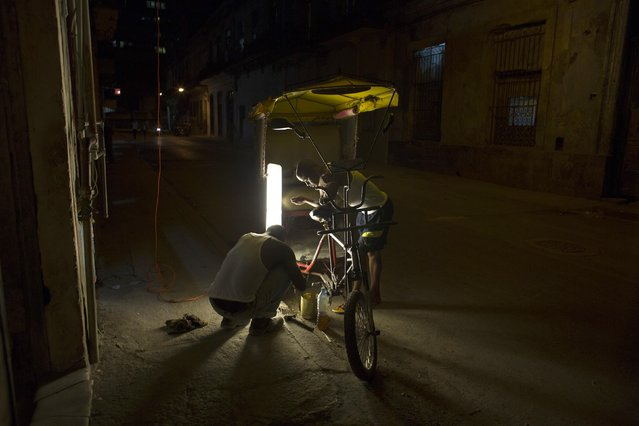 Bicycle taxi drivers fix their vehicle in downtown Havana, December 22, 2014. (Photo by Alexandre Meneghini/Reuters)