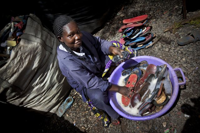 In this photo taken Monday, April 29, 2013, worker Jacqueline Achien washes discarded flip-flops in a bucket prior to them being sorted and carved into toy animals, at the Ocean Sole flip-flop recycling company in Nairobi, Kenya. The company is cleaning the East African country's beaches of used, washed-up flip-flops and the dirty pieces of rubber that were once cruising the Indian Ocean's currents are now being turned into colorful handmade giraffes, elephants and other toy animals. (Photo by Ben Curtis/AP Photo)