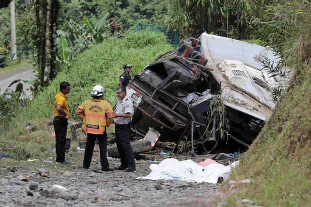 Firefighters chat while standing next to covered bodies and the wreckage of a passenger bus at the site of an accident that left 11 people dead in Cinchona, Costa Rica, October 20, 2016. (Photo by Randall Campos/Reuters)