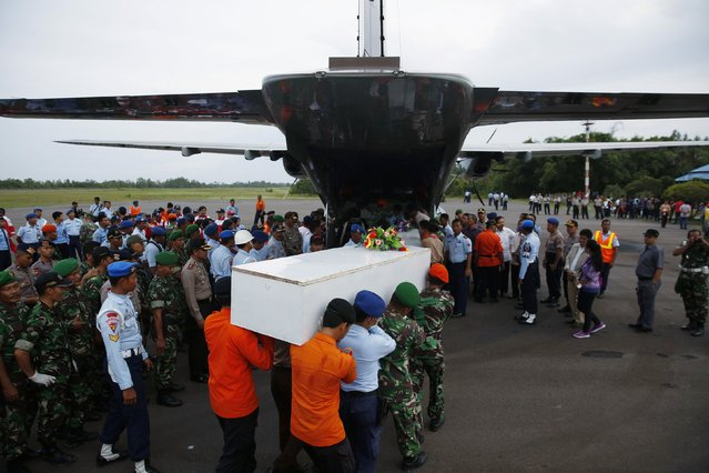 Caskets containing the remains of AirAsia QZ8501 passengers recovered from the sea are carried to a military transport plane before being transported to Surabaya, where the flight originated, at the airport in Pangkalan Bun, Central Kalimantan January 2, 2015. Ships and aircraft criss-crossed the seas off Borneo on Friday hunting for the wreck of the Indonesia AirAsia passenger jet, but bad weather was again hindering the search for the plane and the black box flight recorders that should reveal why it crashed. (Photo by Darren Whiteside/Reuters)