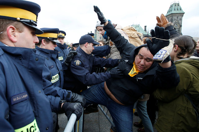 Protestors are pushed by Royal Canadian Mounted Police (RCMP) officers while trying to cross a police barricade during a demonstration against the proposed Kinder Morgan pipeline on Parliament Hill in Ottawa, Ontario, Canada, October 24, 2016. (Photo by Chris Wattie/Reuters)