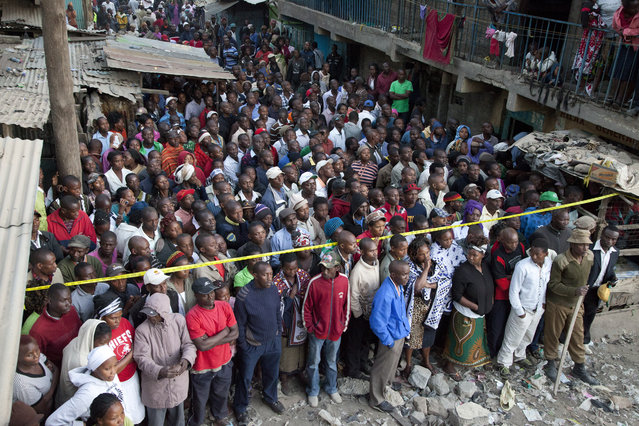 Kenyans watch rescue workers as they look for survivors at the site of the collapsed building in the capital Nairobi, Kenya , Monday, January 5, 2015. The residential building in the Huruma neighborhood of Nairobi collapsed on Sunday and according to the Kenya Red Cross, a dozen people have so far been rescued but an unknown number are still feared trapped. (Photo by Sayyid Azim/AP Photo)