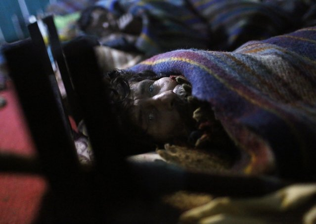 A homeless man covered in a blanket looks on inside a government-run night shelter on a cold winter night in the old quarters of Delhi December 30, 2014. An intense spell of cold weather has forced hundreds of homeless to seek refuge in the shelters. (Photo by Anindito Mukherjee/Reuters)