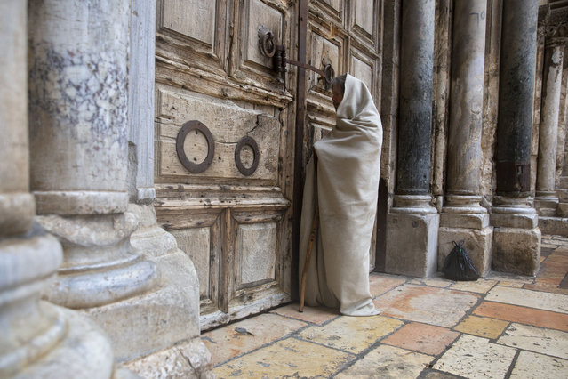A Christian worshiper stands at the closed door of the Church of the Holy Sepulchre, believed by many Christians to be the site of the crucifixion and burial of Jesus Christ, in Jerusalem, Friday, April 10, 2020. Christians are commemorating Jesus' crucifixion without the solemn church services or emotional processions of past years, marking Good Friday in a world locked down by the coronavirus pandemic. (Photo by Sebastian Scheiner/AP Photo)