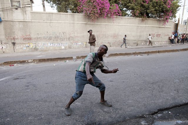 A protester throws a rock during clashes with residents in a demonstration against the results of the presidential elections in Port-au-Prince, Haiti, November 24, 2015. (Photo by Andres Martinez Casares/Reuters)