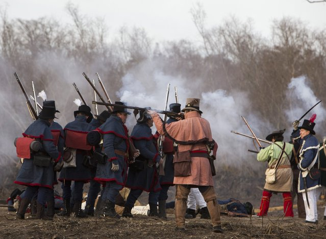 Reenactors playing the roll of Kentucky volunteers, fighting for the United States, fire muskets during a reenactment of the Battle of New Orleans in the War of 1812, marking its bicentennial in Chalmette, Louisiana, January 10, 2015. (Photo by Lee Celano/Reuters)