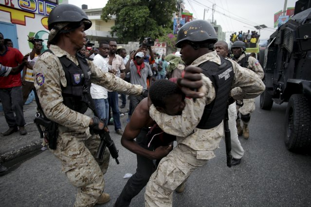 Two National Police officers fight with a detained protestor during a demonstration against the results of the presidential elections in Port-au-Prince, Haiti, November 26, 2015. (Photo by Andres Martinez Casares/Reuters)