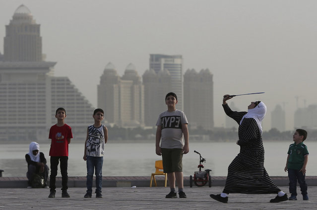 In this Friday, May 4, 2018, photo, a woman plays badminton by the sea with the skyline of Doha, Qatar in the background. The diplomatic crisis gripping the energy-rich country of Qatar, the worst to grip the Gulf region since Iraq's 1990 invasion of Kuwait, will turn a year-old on June 5. (Photo by Kamran Jebreili/AP Photo)
