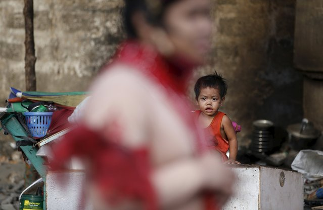 A homeless boy watches a parade by transgender women and government health workers during a World Aids day celebration in Manila, Philippines, December 1, 2015. (Photo by Erik De Castro/Reuters)