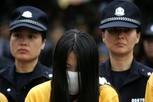 SHENZHEN, CHINA - NOVEMBER 29: (CHINA OUT) Policewomen escort a suspect during a public sentence of suspected criminals accused of dealing with s*x service including prostitution and organizing prostitution, on November 29, 2006 in Shenzhen of Guangdong Province, China. The local authorities have launched a campaign to crack down on prostitution business. According to state media, male and female prostitution are widespread despite being illegal in China. (Photo by China Photos/Getty Images)