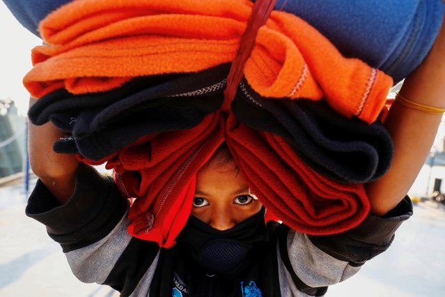 A Rohingya girl carries blankets as she prepares to board a ship to move to Bhasan Char island near Chattogram, Bangladesh, December 29, 2020. (Photo by Mohammad Ponir Hossain/Reuters)