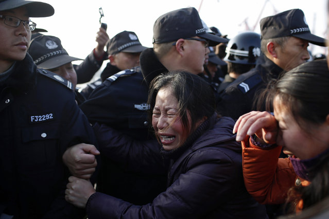 Relatives of a missing person scuffle with police officers on the bank of the Yangtze River, near Jingjiang, Jiangsu province January 17, 2015. (Photo by Aly Song/Reuters)