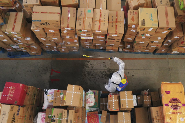 In this photo released by Xinhua News Agency, a worker wearing a protective suit sprays disinfectant the goods at a logistic distribution center in Shijiazhuang in north China's Hebei province on Saturday, January 23, 2021. A Chinese city has brought 2,600 temporary treatment rooms online as the country's north battles new clusters of coronavirus. (Photo by Mu Yu/Xinhua via AP Photo)