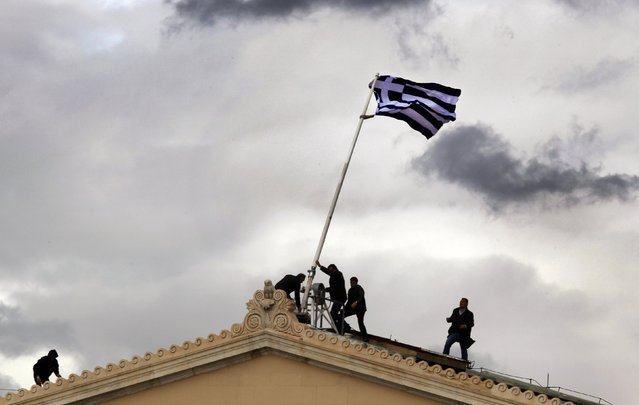 Greek parliament employees raise a mast after they replaced torn-off Greek flag with a new one atop the parliament in Athens Syntagma (Constitution) square in this April 18, 2012 file photo. (Photo by Yannis Behrakis/Reuters)