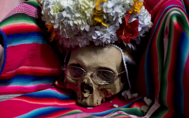 "A  decorated human skull or ""natitas"", sits on a blanket inside the Cementerio General chapel, during the Natitas Festival celebrations, in La Paz, Bolivia, Tuesday, November 8, 2016. (Photo by Juan Karita/AP Photo)"