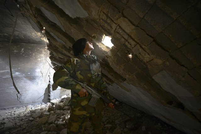 A member of the Libyan pro-government forces, backed by the locals, holds his weapon as he looks through a hole in a wall, during clashes with the Shura Council of Libyan Revolutionaries, in Benghazi January 21, 2015. The Shura Council of Libyan Revolutionaries is an alliance of former anti-Gaddafi rebels who have joined forces with Islamist group Ansar al-Sharia. (Photo by Esam Omran Al-Fetori/Reuters)