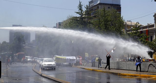 A jet of water is released on demonstrators during a protest against the private system of pension fund administrators in Santiago, Chile, December 10, 2015. (Photo by Ivan Alvarado/Reuters)
