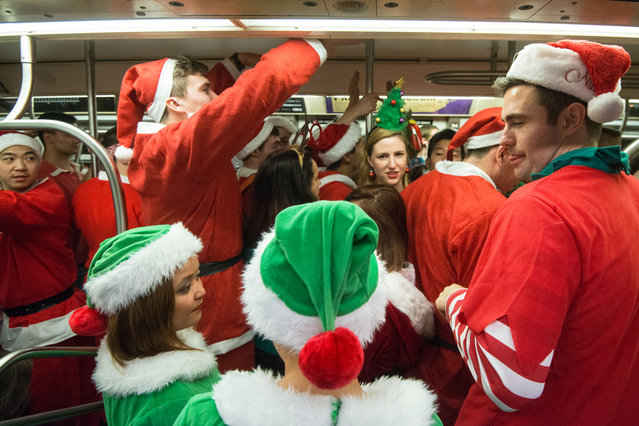 People dressed as Santas board a crowded subway during the annual SantaCon pub crawl December 12, 2015 in the Brooklyn borough of New York City. (Photo by Stephanie Keith/Getty Images)