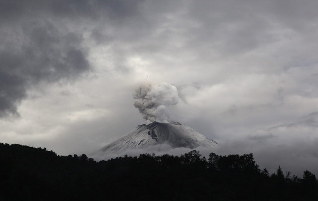 A plume of ash and steam rises from the Popocatepetl volcano as seen from the town of Santiago Xalizintla, Mexico, Sunday, July 7, 2013. Just east of Mexico City, the volcano has spit out a cloud of ash and vapor 2 miles (3 kilometers) high over several days of eruptions. Mexico's National Center for Disaster Prevention raised the volcano alert from Stage 2 Yellow to Stage 3 Yellow, the final step before a Red alert, when possible evacuations could be ordered. (Photo by Marco Ugarte/AP Photo)
