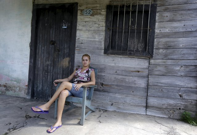 Milena, 23, sits outside her house in Camaguey province, Cuba November 13, 2015. Picture taken November 13, 2015. (Photo by Enrique de la Osa/Reuters)