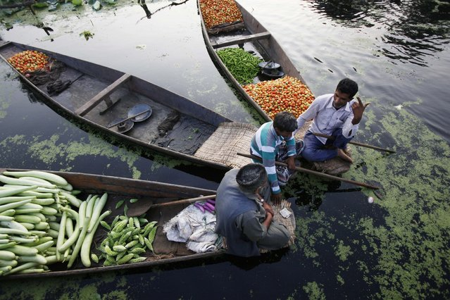 Kashmiri men sit on boats loaded with vegetables at the floating vegetable market on Dal Lake in Srinagar, India, at dawn Sunday, July 28, 2013. Vegetables are grown in numerous floating gardens around the lake, and sold from boats at the market. A variety of different vegetables are grown through all four seasons, making the floating market a daily event throughout the year. (Photo by Greg Baker/AP Photo)