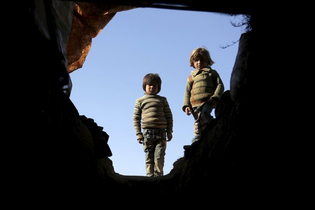 Internally displaced Syrian boys stand at the entrance of their makeshift shelter that is an underground cave in Om al-Seer, southern Idlib countryside, Syria December 26, 2015. (Photo by Khalil Ashawi/Reuters)