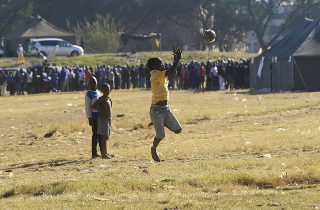 Children play soccer outside a polling station with people queueing to vote in Harare, Zimbabwe, Monday, July 30, 2018. The vote will be a first for the southern African nation following a military takeover and the ousting of former longterm leader Robert Mugabe. (Photo by Tsvangirayi Mukwazhi/AP Photo)