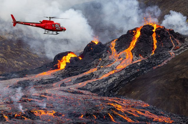 A helicopter flies close to a volcanic eruption which has begun in Fagradalsfjall near the capital Reykjavik on March 20, 2021 in Fagradalsfjall, Iceland. On Friday the Icelandic meteorological office announced a volcano, referring to a mountain located south-west of the Capital Reykjavik has erupted after thousands of small earthquakes in the area over the recent weeks. A no-fly zone has been established in the area. (Photo by Vilhelm Gunnarsson/Getty Images)
