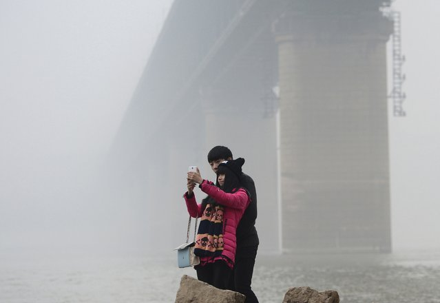 "A couple take a ""selfie"" during a polluted day near a pier on the Yangtze River in Wuhan, Hubei province, January 26, 2015. (Photo by Reuters/China Daily)"