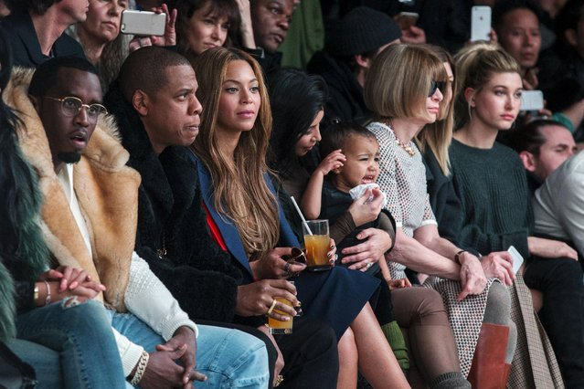 Kim Kardashian attempts to calm her daughter, North, while sitting next to Sean Combs (L), Jay-Z (2nd L), Beyonce (3rd L) and Anna Wintour (2nd R) as they watch a presentation of Kanye West's Fall/Winter 2015 partnership with Adidas at New York Fashion Week in New York, United States February 12, 2015. (Photo by Lucas Jackson/Reuters)