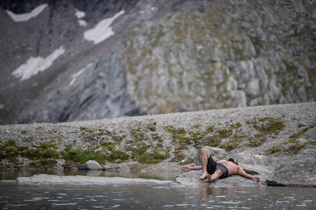Ice swimmer Gerhard relaxes after he swum in a filled up water kettle in an ice cave inside the Nature Ice Palace, with a hight of 3,250 meters (10,663 feet) above sea level, at Hintertux Glacier near Hintertux, some 480 kilometers (298 miles) western of Vienna, Austria, 27 July 2018. (Photo by Christian Bruna/EPA/EFE)