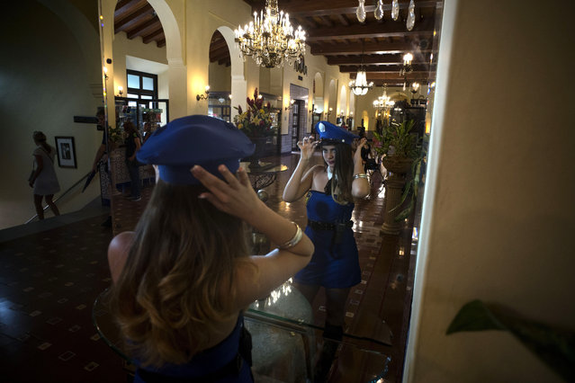 In this December 5, 2015 photo, Yunailey Dopico Martinez, 14, who lives in Cuba, adjusts her hat during a quinceanera photo session at the National Hotel in Havana, Cuba. The daughters of workers in Cuba's emerging private sector are helping fuel business. With the economic reforms, many families on the island now have extra cash to spend for quniceanera celebrations. (Photo by Ramon Espinosa/AP Photo)