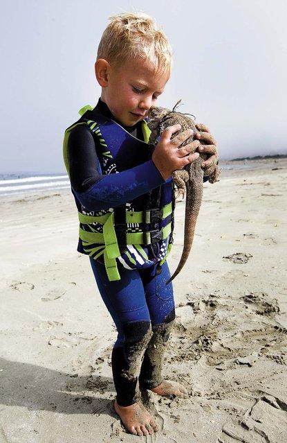 Triston plays with a tourist's on the beach. (Photo by Joe Johnston/The Tribune of San Luis Obispo)