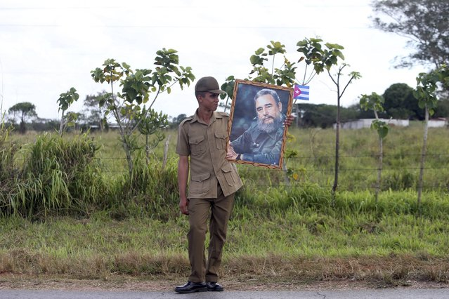 A soldier stands along a highway while waiting for the ashes of Fidel Castro to pass during a three-day journey to the eastern city of Santago, in Cardenas, Cuba, November 30, 2016. (Photo by Edgard Garrido/Reuters)