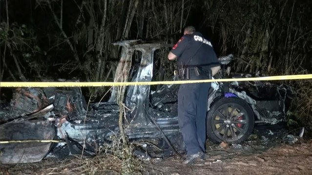 The remains of a Tesla vehicle are seen after it crashed in The Woodlands, Texas, April 17, 2021, in this still image from video obtained via social media. Video taken April 17, 2021. (Photo by Scott J. Engle via Reuters)