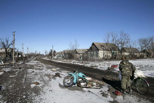 A man pushes a bicycle along buildings damaged by fighting in the village of Nikishine, south east of Debaltseve February 17, 2015. (Photo by Baz Ratner/Reuters)