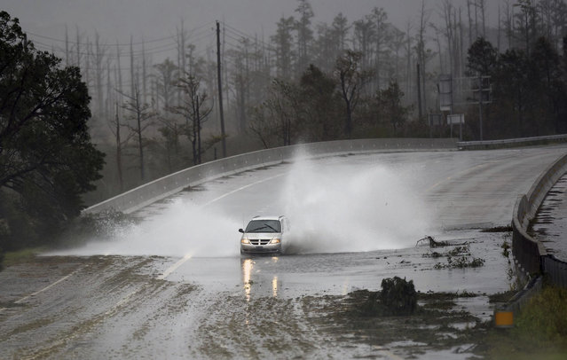 A car drives through water caused by the rain from Florence, now a tropical storm on U.S. 74/76 in Leland, N.C., Saturday, September 15, 2018. The rain from Hurricane Florence was expected to continue through Sunday. (Photo by Matt Born/The Star-News via AP Photo)