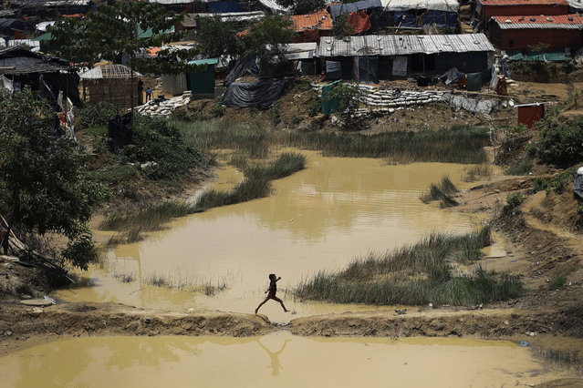 In this Thursday, June 28, 2018, file photo, a Rohingya child jumps across a gap as he makes his way across muddy waters in Balukhali refugee camp, Bangladesh. (Photo by Wong Maye-E/AP Photo/File)