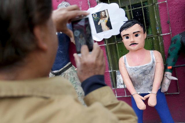 """A pedestrian takes a photo with his cellphone of a pinata depicting the drug lord Joaquin """"El Chapo"""" Guzman outside a workshop in Reynosa, in Tamaulipas state, Mexico, January 13, 2016. (Photo by Daniel Becerril/Reuters)"""