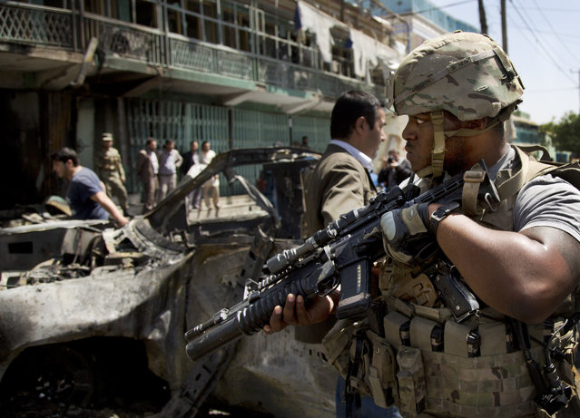 A U.S. soldier arrives at the scene where a suicide car bomber attacked a NATO convoy in Kabul, Afghanistan on May 16, 2013. A Muslim militant group, Hizb-e-Islami, claimed responsibility for the powerful explosion that killed and wounded many and rattled buildings across Kabul. (Photo by Anja Niedringhaus/AP Photo/File)