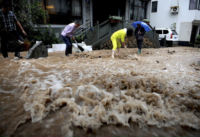Residents dig a channel to prevent floodwater from reaching their homes in Hangzhou, in east China's Zhejiang province, Monday, October 7, 2013. A typhoon slammed into southeastern China on Monday with powerful winds and heavy rains that killed at least five people, cut power, canceled flights and suspended train services. (Photo by AP Photo)