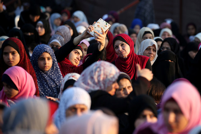 Palestinian women take a selfie as others wait for prayers on the first day of Eid al-Adha festival, in Gaza City August 21, 2018. (Photo by Ibraheem Abu Mustafa/Reuters)