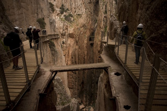"""Journalists and visitors walk during a visit to the foot-path """"El Caminito del Rey"""" (King's little path) a narrow walkway hanging and carved on the steep walls of a defile in Ardales near Malaga on March 15, 2015. (Photo by Jorge Guerrero/AFP Photo)"""