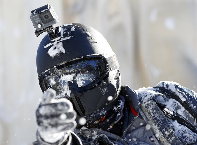 A man tosses a snowball while wearing a full helmet and GoPro, during an organized snowball fight at Dupont Circle Sunday, January 24, 2016 in Washington. (Photo by Alex Brandon/AP Photo)