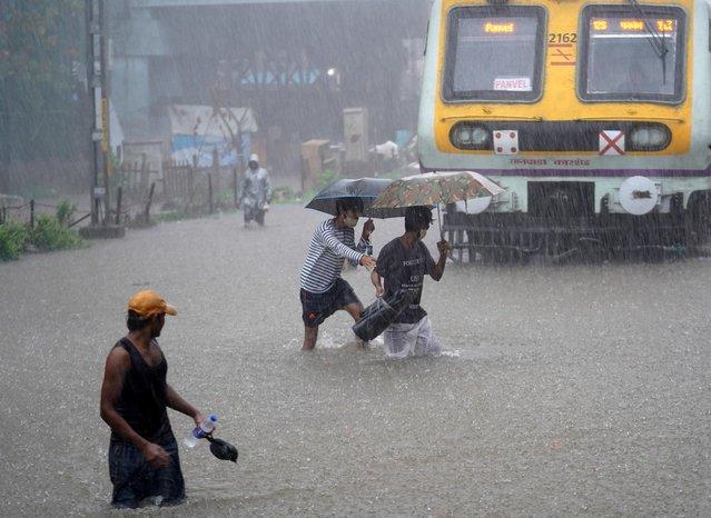 People cross waterlogged railway tracks next to a parked passenger train during heavy rains in Mumbai, India, June 9, 2021. (Photo by Hemanshi Kamani/Reuters)