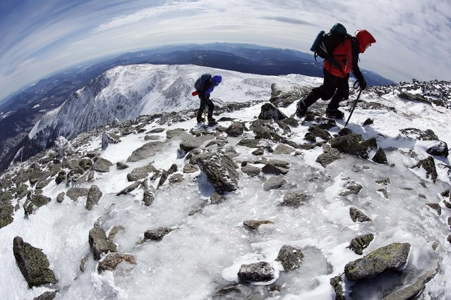 In this Tuesday, March 10, 2015 photo, Gary Gustafson, 58, leads Linda Dewey, 54, up an icy trail on the summit cone of Mount Washington in New Hampshire. The hikers waited about four weeks for a calm day before attempting the mountain that is notorious for its erratic weather. (Photo by Robert F. Bukaty/AP Photo)