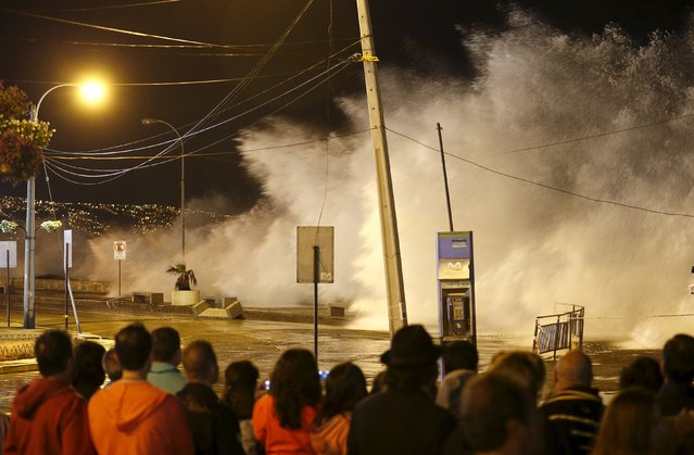 Tourists watch high waves of the Pacific Ocean pounding the coast  in Vina del Mar city, Chile January 25, 2016. (Photo by Rodrigo Garrido/Reuters)