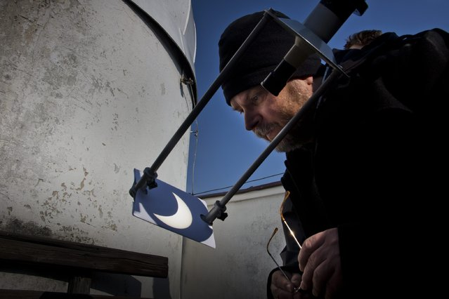 A student observes the shadow of a partial eclipse cast on to white paper, at the Astronomical Observatory in Bialystok, Poland March 20, 2015. (Photo by Agencja Gazeta/Reuters)