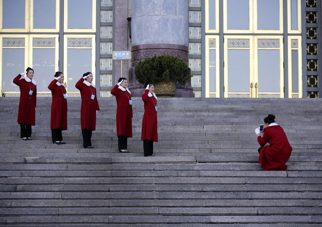 Hotel guides pose for photographs in front of the Great Hall of the People during the third plenary meeting of Chinese People's Political Consultative Conference (CPPCC) in Beijing, March 11, 2015. (Photo by Kim Kyung-Hoon/Reuters)