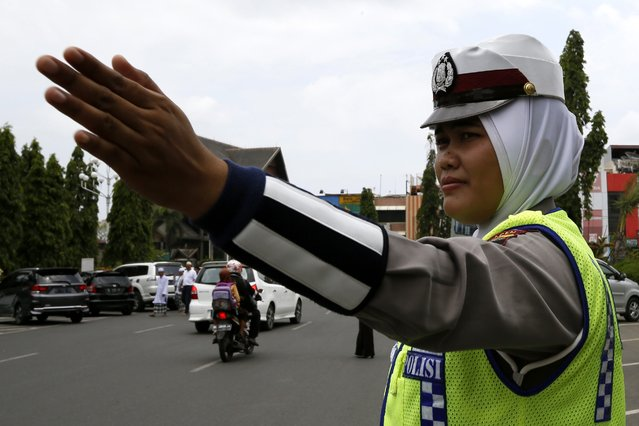 An Acehnese female police officer wear a hijab on duty in the street in Banda Aceh, Indonesia, 27 March 2015. Indonesia National Police officially issued a regulation allowing female police officer to wear the Islamic hijab (heads craft) as a part of their uniform. Indonesia is the biggest Muslim population in the world. (Photo by Hotli Simanjuntak/EPA)